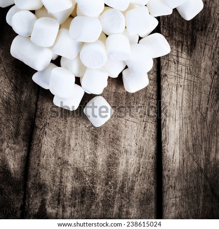 White Fluffy Round Marshmallows on wooden vintage background with free blank copy space for text. Sweet Food Candy Background  - stock photo