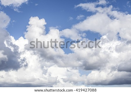 White fluffy storm clouds in blue sky - stock photo