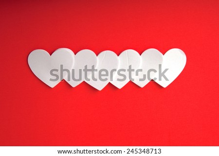 White foam hearts on a red background.