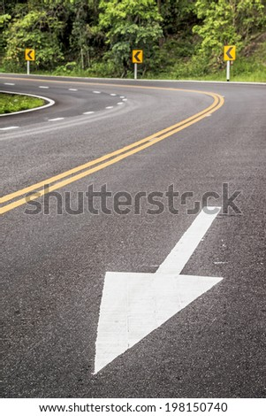 White forward arrow on the street at dangerous curve.  - stock photo