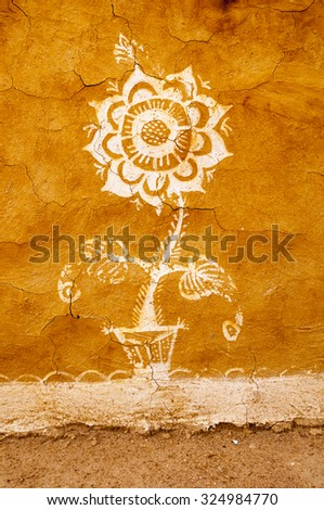 White fower at the dried clay wall, India - stock photo