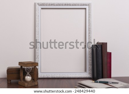 White frame with books and wooden hourglass on a table - stock photo