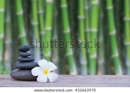 white frangipani flower and stone zen spa on wood with blurred Bamboo trees background - stock photo