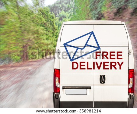 White free delivery Van driving fast on forest road - stock photo