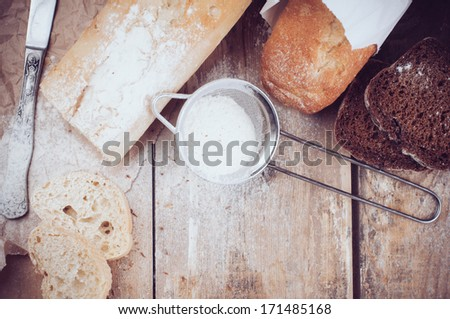 White french baguette and fresh rustic loaf of wholemeal rye bread, sliced �¢??�¢??and flour on a wooden board, bakers, food background is.