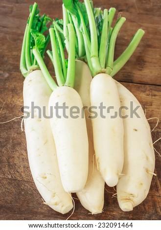white fresh radish on wooden table - stock photo