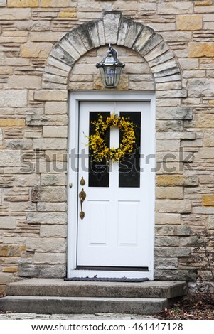 White front door close-up. White front door with two stairs of an old style brick house, decorated with yellow season wreath and outdoor lantern over it. Vertical shot.