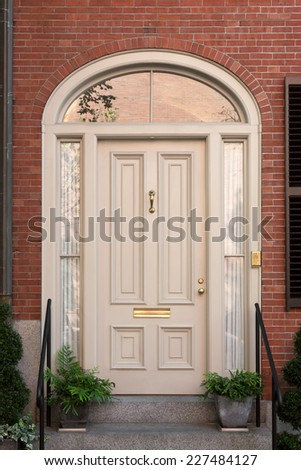 White Front Door with Surrounding White Arch with Lunette and Potted Plants