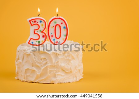 White frosted cake with 30 lit candles.  30th birthday cake - stock photo