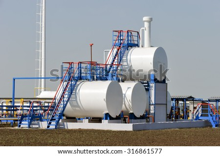 White fuel tanks in natural gas treatment plant in bright sunny summer day