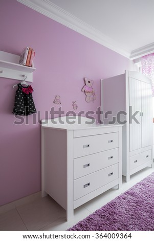 White furniture and rose wall in baby's room