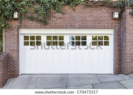 White garage door surrounded by green ivy