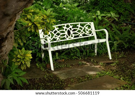 WHITE GARDEN BENCH Bright White Iron Chair Placed In Front Of The Green  Bush Under The