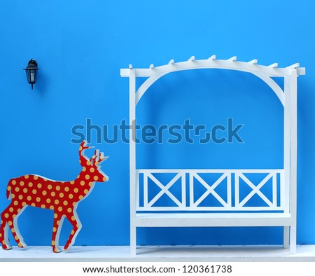 White garden chair and red deer on blue background - stock photo