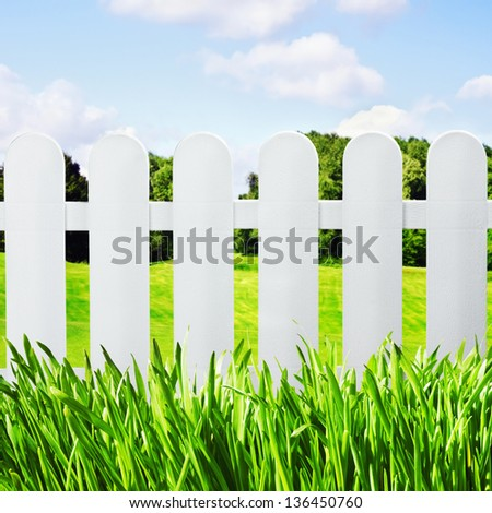 white garden fence on the lawn overlooking the green field and forest