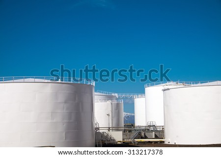 White gas storage tanks in front of a blue sky
