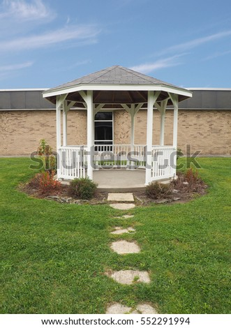 white gazebo by a brick building