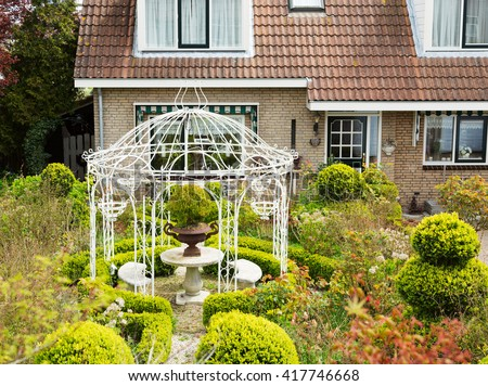 White gazebo in the courtyard of a cozy cottage in the village. - stock photo