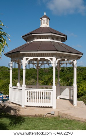 white gazebo on a tropical park with pathway (blue sky background) - stock photo