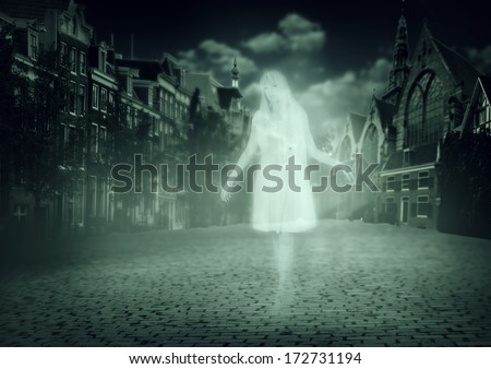 white ghost of a woman walking down the street of the old town - stock photo
