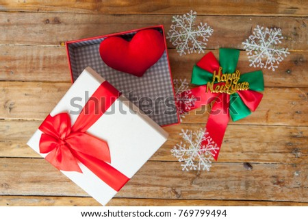 White gift box and red ribbon and mini heart inside on wood background with space.