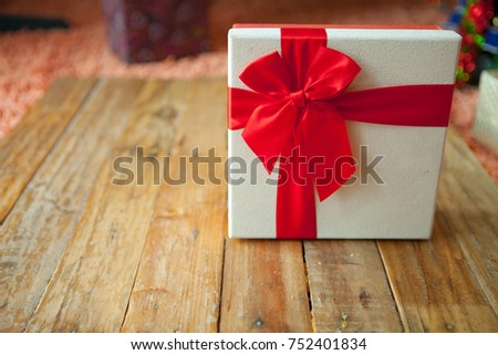White gift box and red ribbon  on wood background with space.