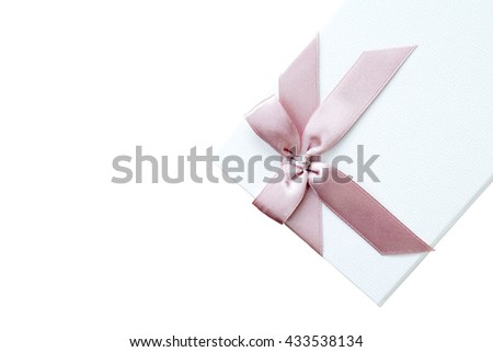 White gift box decorated with a pink bow on an isolated white background with copy space and a clipping path