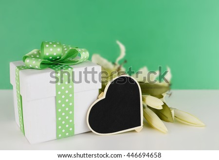 White gift box decorated with green polka dot ribbon. White silk lilies lay beside the box with a heart shaped blackboard on white table with green background. Shallow depth of field - stock photo