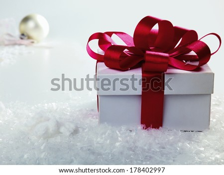 white gift box in fresh snow against a background bokeh