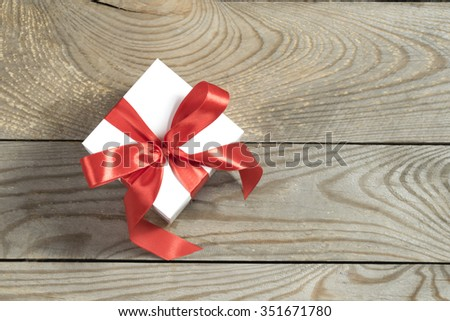 white gift box on wooden background - stock photo