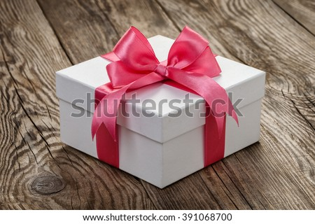 White gift box with a pink ribbon on the old board. - stock photo