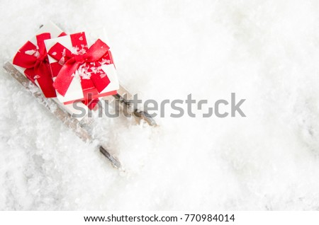 white gift box with a red bow on sleigh in the snow