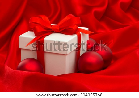 White gift box with christmas balls decoration over red silk background - stock photo