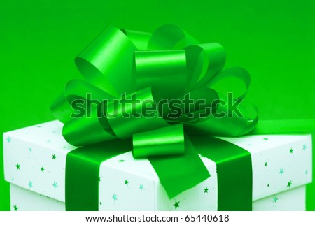 White gift box with green ribbon isolated on green background - stock photo
