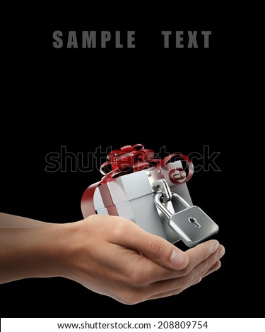 white gift box with red ribbon and bow. Man hand holding object  isolated on black background. High resolution  - stock photo