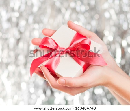 White gift box with red ribbon in hands over sparkling background - stock photo