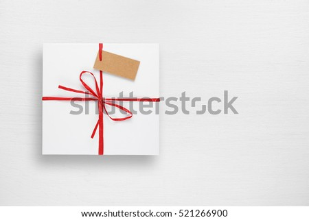 White gift box with tag on white table top view