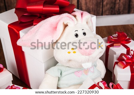 white gift boxes and soft toy on a wood background
