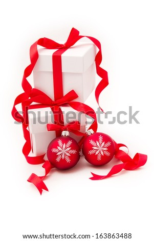White gift boxes with red curly ribbons and christmas balls