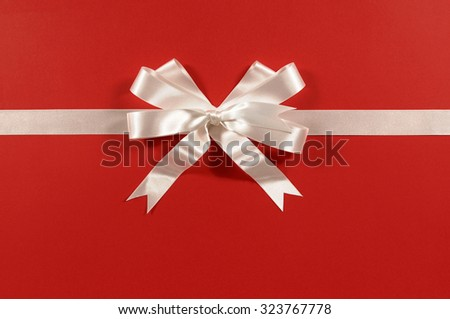 White gift ribbon bow on red wrapping paper background horizontal - stock photo