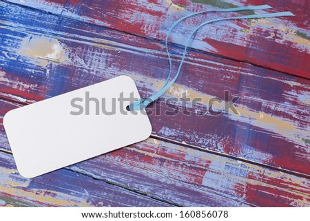 White  gift tag with cotton thread against colored background - stock photo