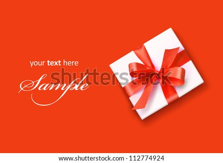 White gift with red ribbon bow isolated on red