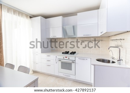 White glossy modern kitchen with stone counter and built-in household appliances in bright colors interior