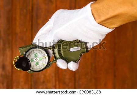 White gloved hand holding a compass for direction, with the old wooden wall as a backdrop. - stock photo