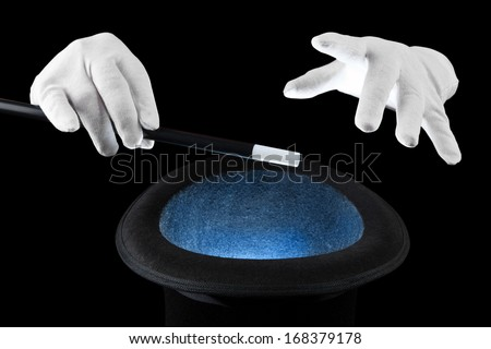 White gloved hands conjure over a magic hat. - stock photo