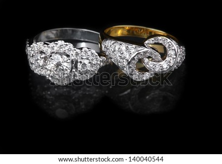 White gold diamond ring and Golden diamond ring on black background - stock photo