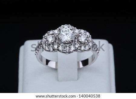 White gold diamond ring with stand on black background