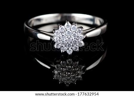 White gold ring with diamonds shot on black surface, macro - stock photo