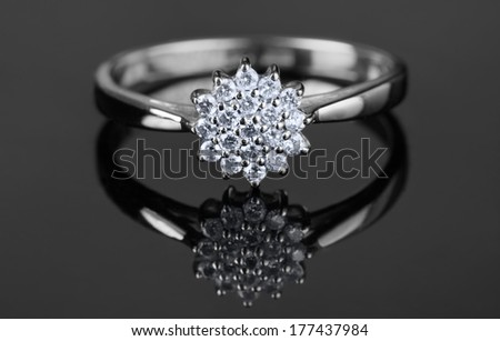 White gold ring with diamonds shot on grey surface, macro - stock photo