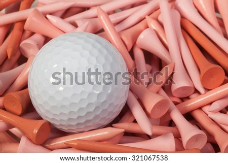White golf ball lying between pink wooden golf tees - stock photo